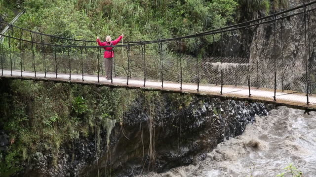 pan across to female hiker crossing suspension bridge - kletterausrüstung stock-videos und b-roll-filmmaterial