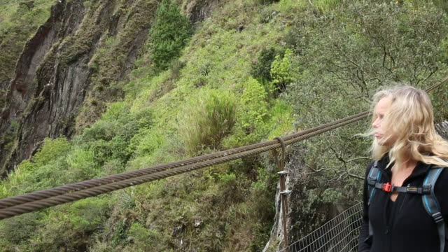 Pan across to female hiker crossing suspension bridge