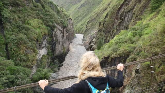 pan across to female hiker crossing suspension bridge - einzelne frau über 40 stock-videos und b-roll-filmmaterial