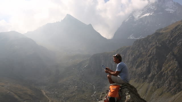pan across to hiker perched on pinnacle, using digital tablet - rucksack stock videos & royalty-free footage