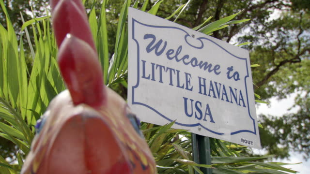 pan across to reveal close-up of welcome to little havana usa sign - マイアミ点の映像素材/bロール