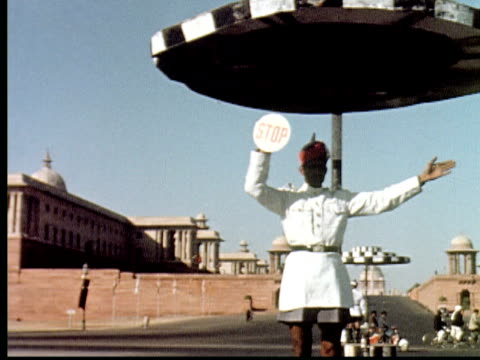 vidéos et rushes de 1960 montage pan across two large palace type buildings in mumbai with traffic cop / mumbai, india - montrer la voie