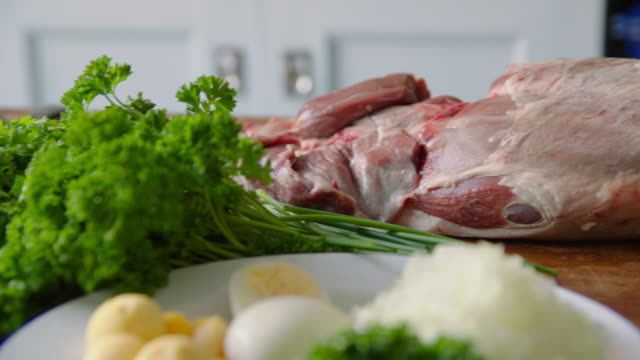 Pan across unprepared food on a kitchen counter: parsley, hard-boiled egg, chopped onion and a raw leg of mutton, UK.