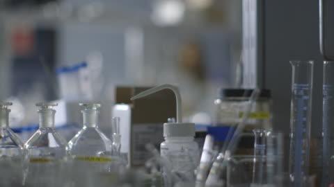 vídeos de stock, filmes e b-roll de pan across various apparatus in a laboratory. - artigos de vidro de laboratório