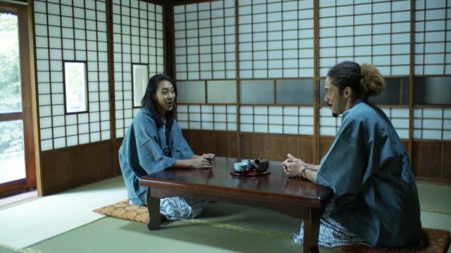 stockvideo's en b-roll-footage met pan over jong paar wachten op maaltijd in ryokan - ryokan