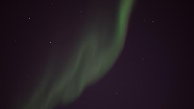 vídeos de stock e filmes b-roll de pan along aurora borealis in starry arctic sky - aurora polar