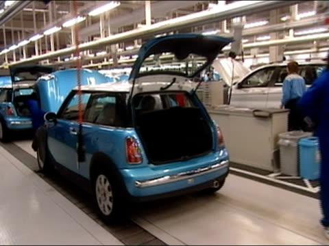 pan along bmws and minis on assembly line to bmw sedan at end driving off line / tokyo, japan - 自動車ブランド mini点の映像素材/bロール