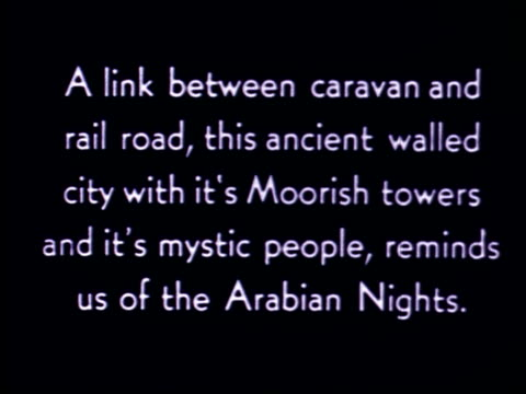 Pan along old stone city walls of Marrakech / Traveling shot past palm trees and desert / Moorish towers with arab bedouins walking by in robes /...