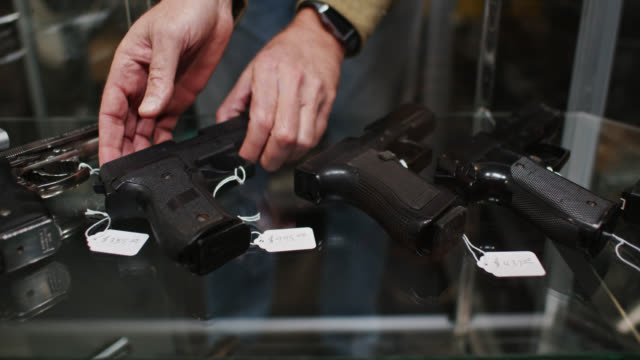 stockvideo's en b-roll-footage met pan along row of handguns in display case with owner's hands showing one item - vuurwapenwinkel