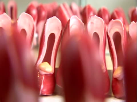 pan along rows of small shoes made from pink chocolate - femininity stock videos & royalty-free footage