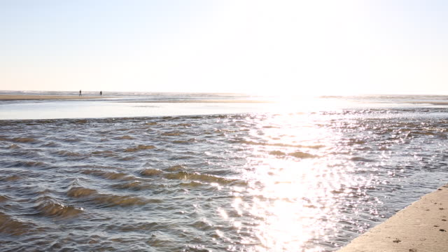 pan along tidal stream out to ocean at sunrise - bay of water stock videos & royalty-free footage