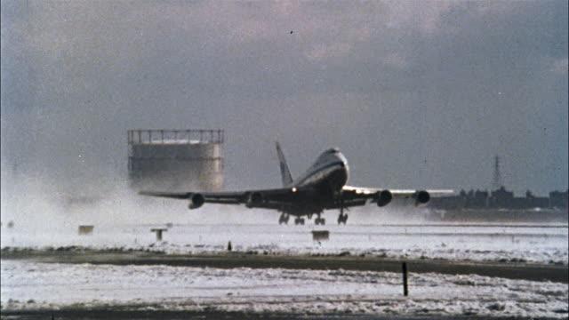 vidéos et rushes de a pan am 747sp takes off from a snowy runway and flies into blue sky. - piste d'envol