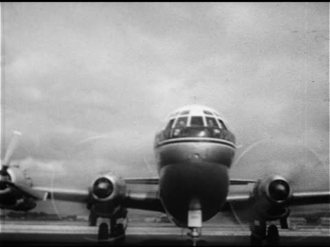 vidéos et rushes de pan american boeing 377 stratocrusier commercial aircraft airliner taxiing on tarmac vs local hawaiian women dancing hula welcome dance tropical... - 1953