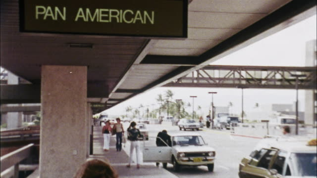 Pan American travelers get their flight tickets, arrive at an airport, check their luggage, and greet a stewardess as they board their airplane.