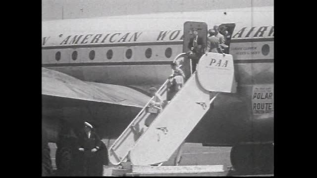 pan american world airlines plane taxies / passengers down stairs see polar route sign on plane - air vehicle stock videos & royalty-free footage