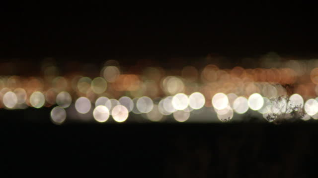 pan and pull focus across lights of a city skyline - urban sprawl stock videos & royalty-free footage