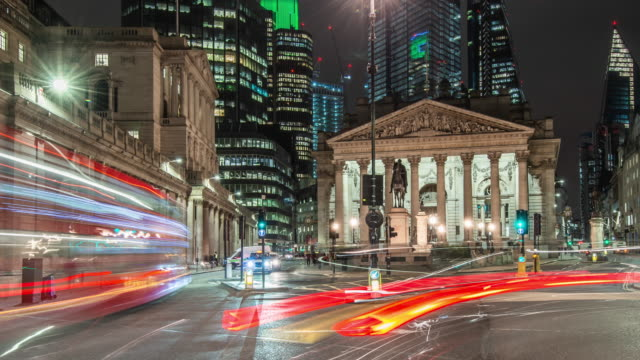 pan and tilt move towards the bank of england as early morning rush hour city traffic moves rapidly passed the royal exchange with silhouetted skyscrapers in the background - バンク オブ イングランド点の映像素材/bロール