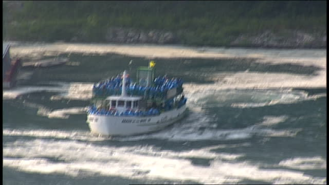 vídeos de stock e filmes b-roll de pan and zoom of boat of tourists going to niagara falls - barco de passeio maid of the mist