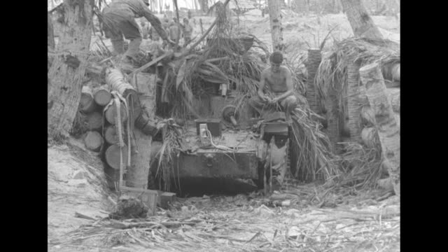 stockvideo's en b-roll-footage met pan arid island with palm trees tanks and us marines standing around / ms camouflaged tank with two marines on it / pile of junk with body on top... - pacifische eilanden