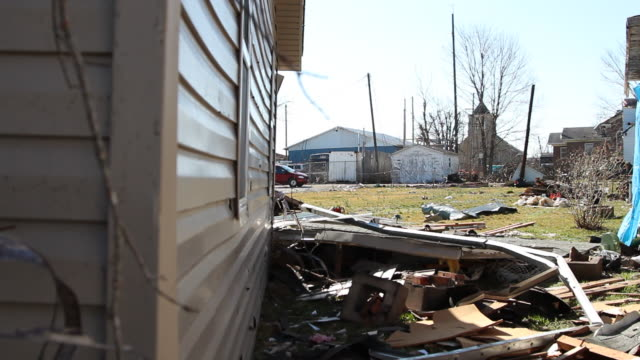 Pan Around Corner Of Damaged Building To Car Driving Away