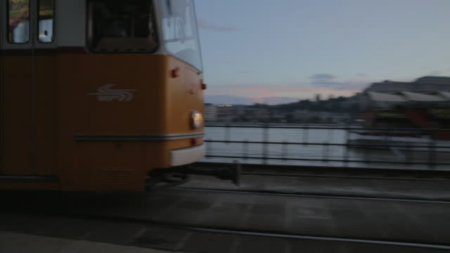 vidéos et rushes de pan as 2 tram travels south to north in budapest - budapest