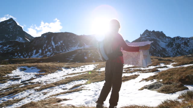 Pan as hiker checks map by mountain range, sunrise