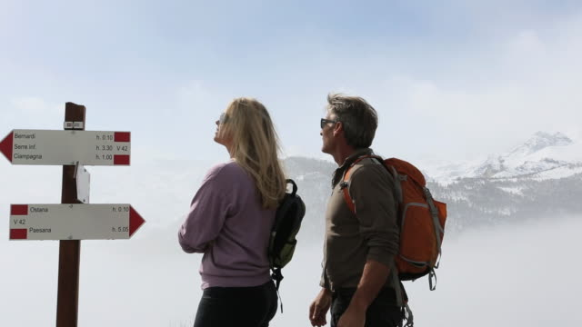 Pan as hikers arrive at signpost, continue on, mtns and fog