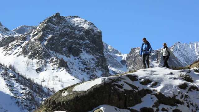 Pan as hikers walk along snowy ridge, look to view