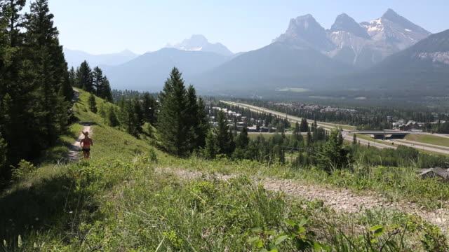 vídeos y material grabado en eventos de stock de pan as teen runs along rolling trail, mountains behind - sólo una adolescente