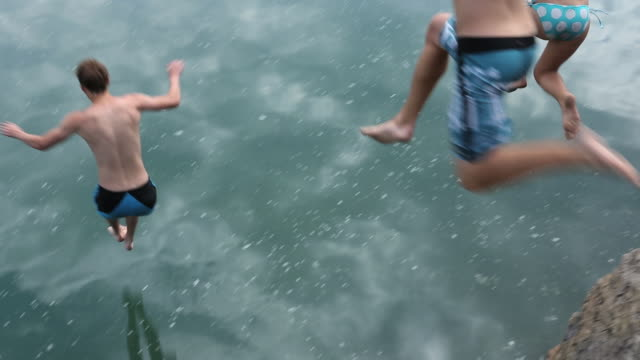 pan as three teen friends jump into mountain lake - swimming stock videos & royalty-free footage