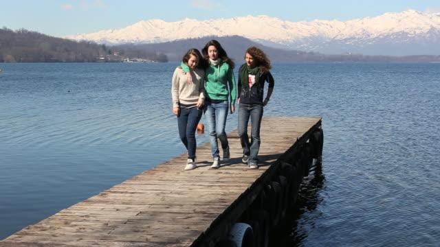 pan as three teen  girls walk up pier, mountain lake - arm umlegen stock-videos und b-roll-filmmaterial