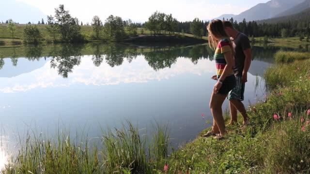 vídeos de stock, filmes e b-roll de pan as two teen friends walk to edge of mountain lake, meadow - short curto