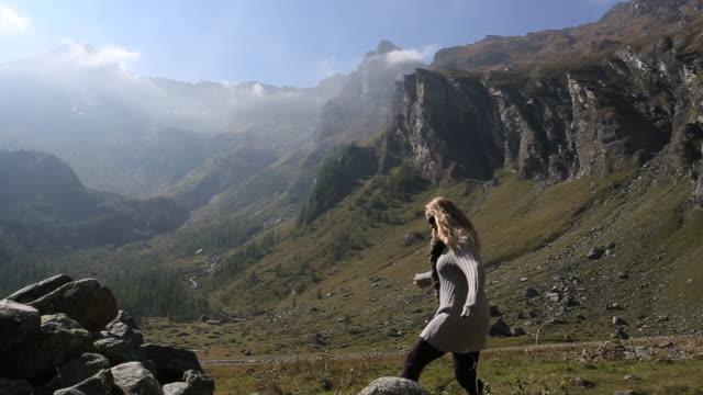 pan as woman walks onto rock pile in mtn meadow - solo una donna di età media video stock e b–roll