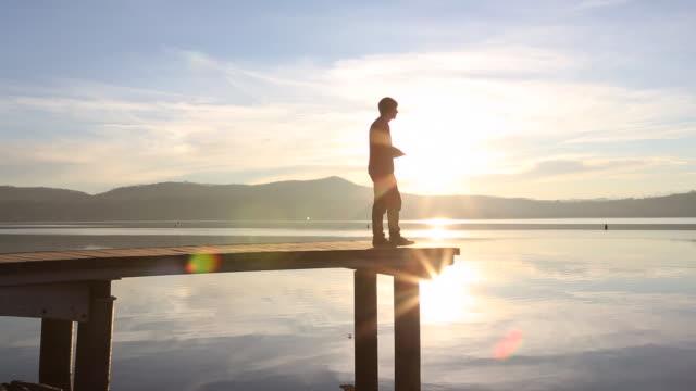 Pan as young man walks along pier texting, ducks enter