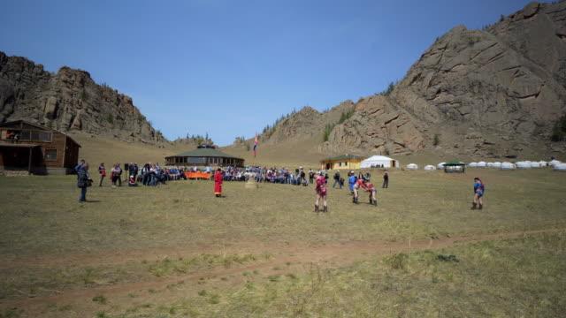pan: audience around wrestlers fighting on field during naadam - ulaanbaatar, mongolia - film festival stock videos & royalty-free footage