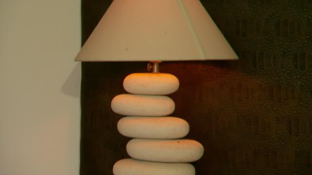 vídeos y material grabado en eventos de stock de pan base to top of a unique lampshade stand large pebbles stacked offcentre - pantalla de lámpara