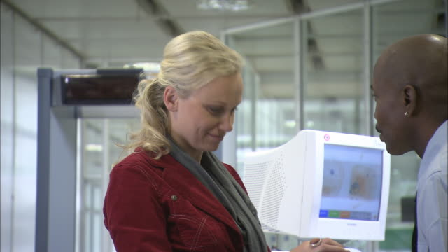 ms pan being scanned by metal detector at airport security checkpoint/ woman showing security guard the contents of her backpack/ munich, germany - säkerhetsskanner bildbanksvideor och videomaterial från bakom kulisserna