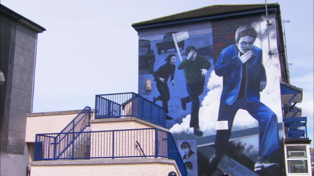 Pan between two Troubles' murals on house, Derry, Northern Ireland