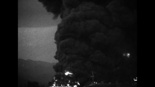 pan billowing clouds of black smoke / flames leap into air from oil tanks surrounded by clouds of black smoke / aerials covering huge fire and... - 1926 stock videos & royalty-free footage