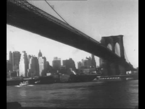 Pan Brooklyn Bridge in New York City NY with barge passing underneath and lower Manhattan skyline in background / montage black men unload cases of...