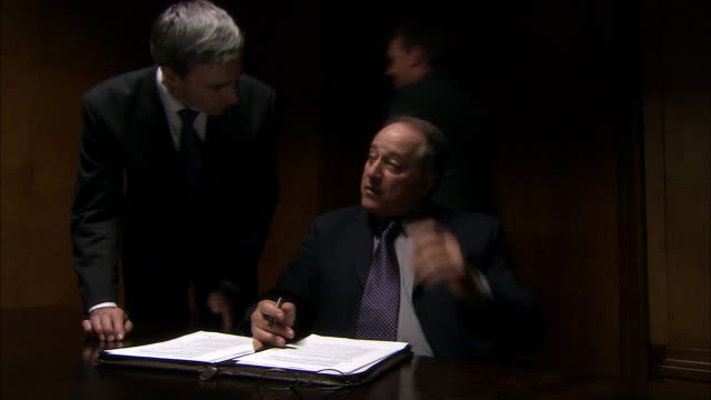 ms pan businessman sitting in dark office as four people bring him documents to look at and sign/ london  - cinematography stock videos & royalty-free footage
