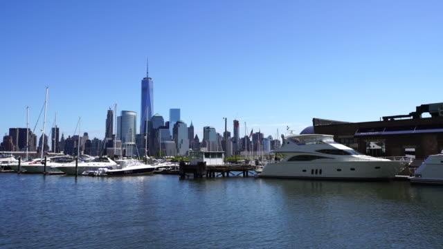 Pan Camera captures Manhattan skyscrapers behind yachts and cruiser boats at Newport Marina at Newport Jersey City New Jersey.