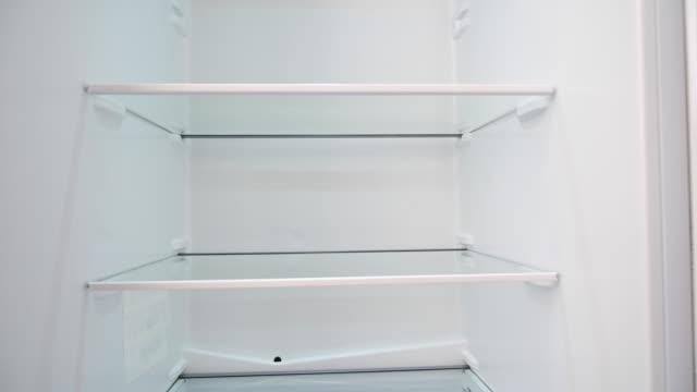 vídeos de stock e filmes b-roll de pan camera movement of an empty refrigerator. - crise mundial de alimentos