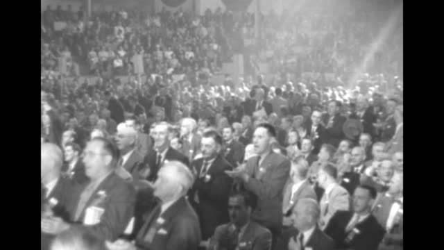 Pan cheering and clapping delegates on convention floor at the Ottawa Coliseum / LS men on podium making announcement photographers all around them...