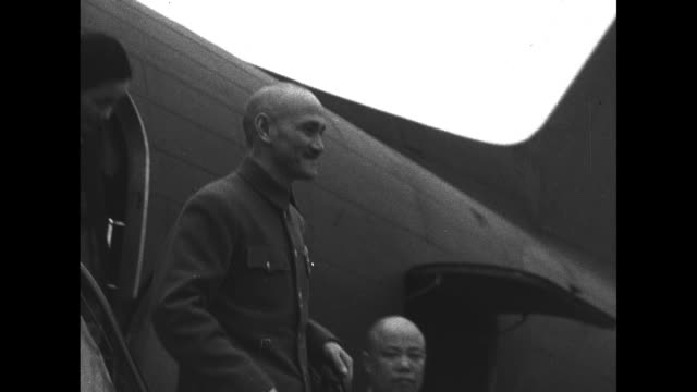 pan chinese troops who stand at attention to plane landing / general chiang kaishek and his wife soong meiling deplane and shake officer's hand then... - chiang kai shek stock-videos und b-roll-filmmaterial