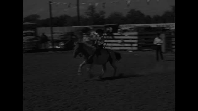 pan circle of cowgirls on horseback / cu woman sitting on tailgate feeding baby hands him over to the father / vs women ride bucking broncos / woman... - bocksprång bildbanksvideor och videomaterial från bakom kulisserna