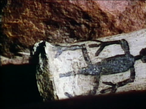 1975 pan close up head-to-head figures carved on rock at / Mesa Verde, Colorado