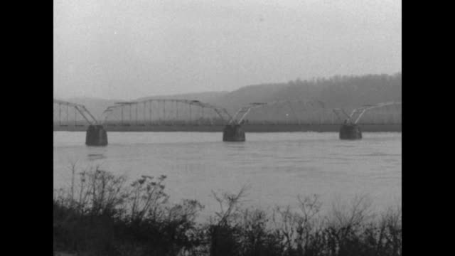 pan conowingo bridge over the susquehanna river / men walk on bridge planks and place explosives / man places nitroglycerin on girder / man detonates... - 起爆装置点の映像素材/bロール