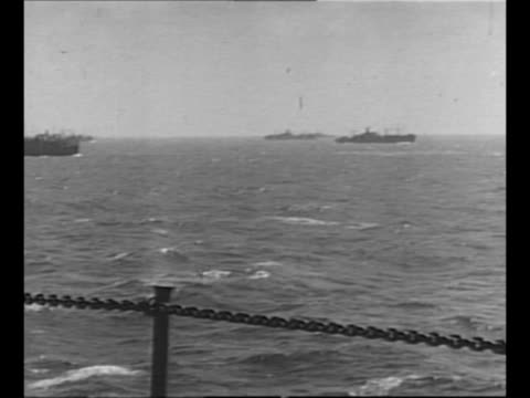 pan convoy of military ships, as seen from deck of camera ship with muzzle of its gun at left as battle for kwajalein atoll begins during world war... - naso di animale video stock e b–roll