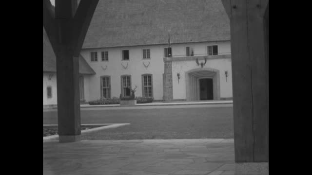 pan courtyard of nazi military leader hermann goering's hunting lodge carinhall with stag statues and antlers on lodge / goering and italian air... - hermann goering stock videos and b-roll footage
